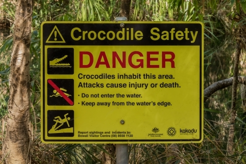 Yellow, red and black sign warning about danger of crocodiles in the water