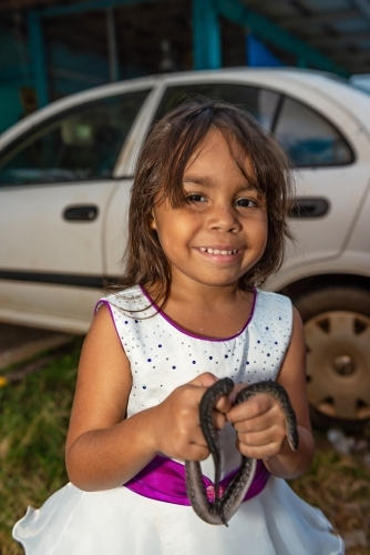 Young aboriginal girl holding pet snake