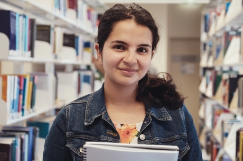 Young adult student in university library