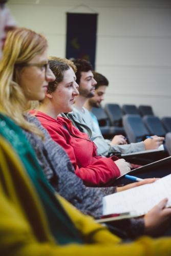 Young adult students listening to professor a university lecture hall