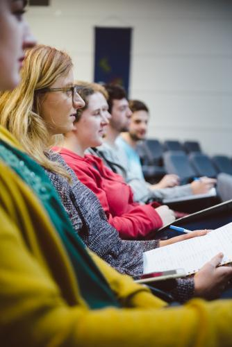 Young adult students sitting in a university lecture hall
