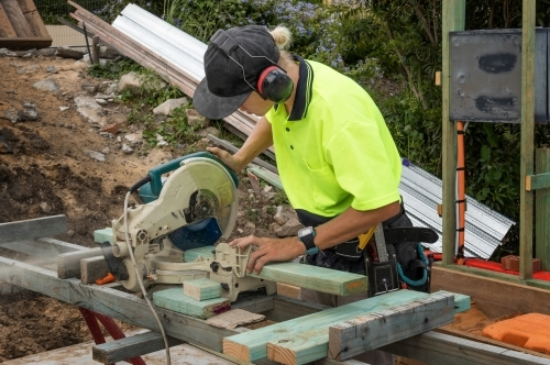 Young apprentice builder cutting length of timber with drop saw on residential construction site