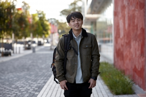 Young Asian student looking at camera on-campus at university