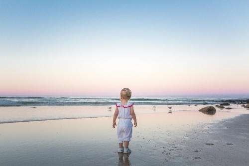 Young blond girl playing at the beach