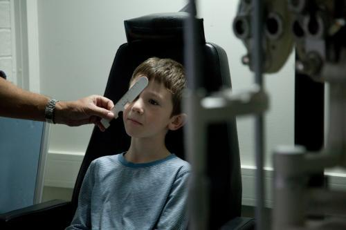 Young boy at an optometrist appointment getting his vision tested