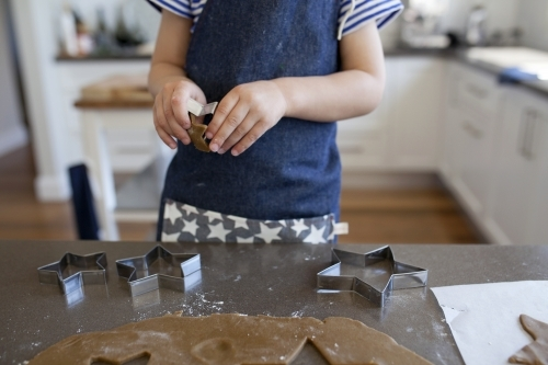 Young boy baking gingerbread biscuits in kitchen at home