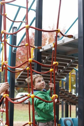 Young boy climbing on play equipment at the park