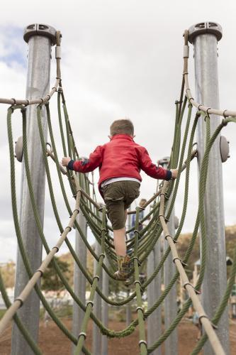 Young boy climbing playground equipment at park