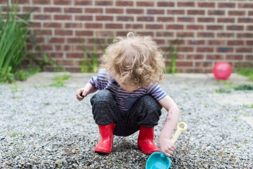 Young boy digging in the wet gravel with a spade