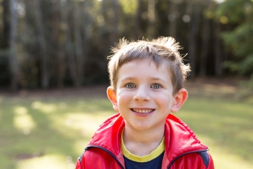 Young boy grinning at camera in forest