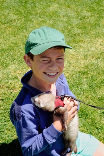 Young boy holding pet ferret at country show