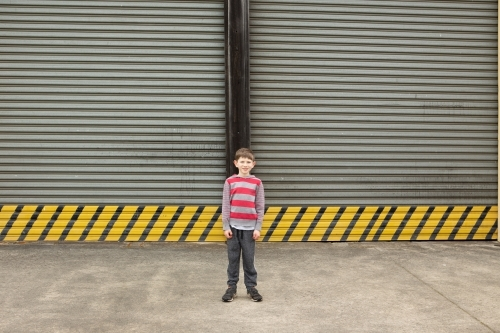 Young boy in front of large roller door