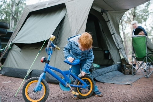 Young boy inspecting his bike at a camp site