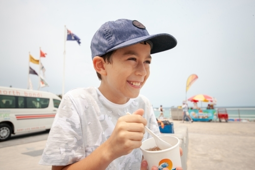 Young boy laughing whilst eating snow cone at beach