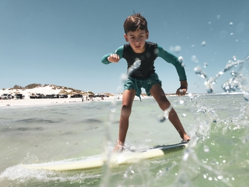 Young boy learning to surf on longboard with sprays of water on lens