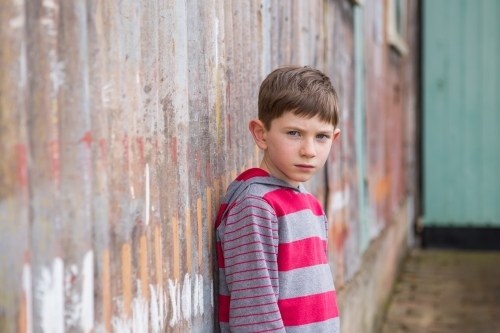 Young boy looking at camera in front of rusty iron wall