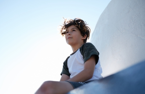 Young boy looking out to a view whilst seated