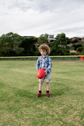 Young boy playing AFL at the park oval