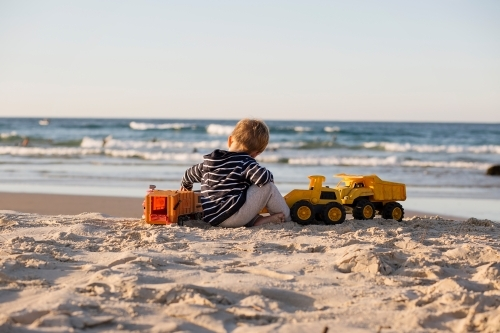 Young boy playing with toy trucks on the beach
