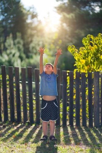 Young boy reaching up to grab the sunshine