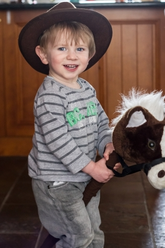 Young boy riding toy horse and smiling for camera