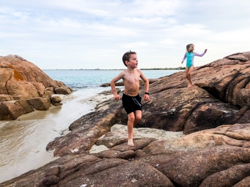 Young boy running over coastal rocks with young girl following him
