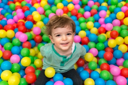 Young boy sitting in a playpen filled with colourful balls