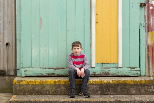 Young boy sitting in front of yellow door