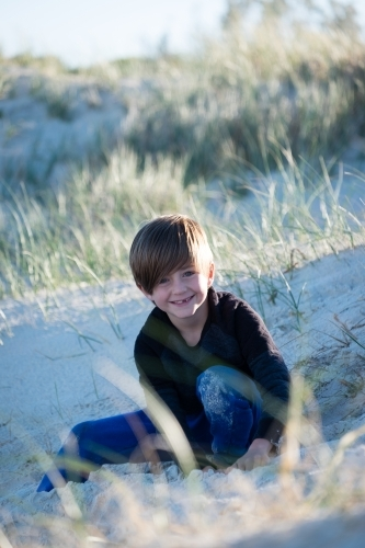 Young boy sitting in the sand dunes smiling