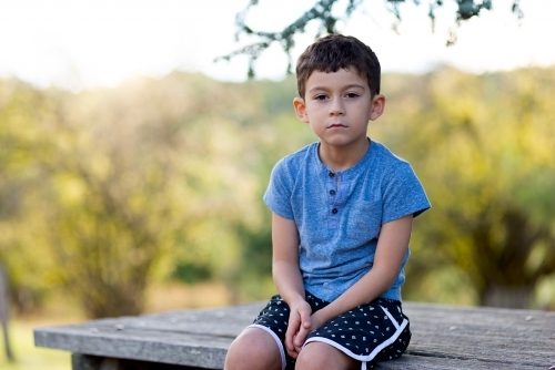 Young boy sitting on bench with nature behind