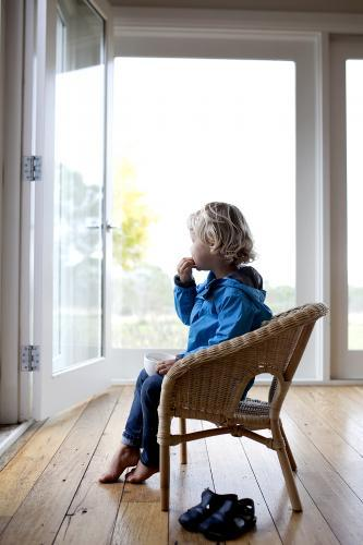 Young boy sitting on chair, eating and looking outside
