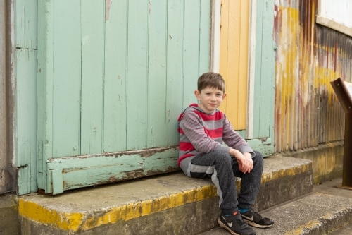 Young boy sitting on step
