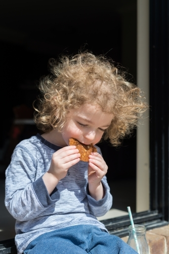 Young boy sitting outside eating a homemade ANZAC biscuit