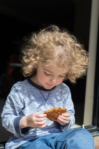 Young boy sitting outside with a homemade ANZAC biscuit