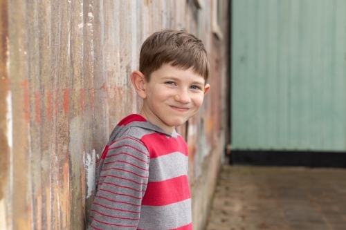 Young boy smiling at camera in front of rusty wall