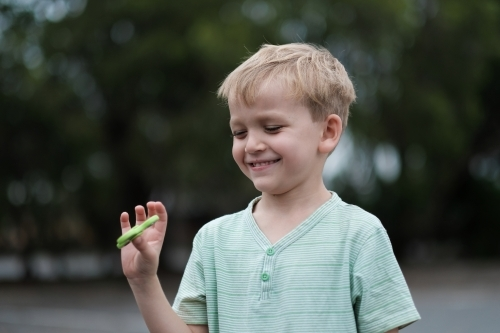 Young boy smiling playing with fidget spinner