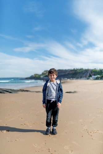 Young boy standing on beach