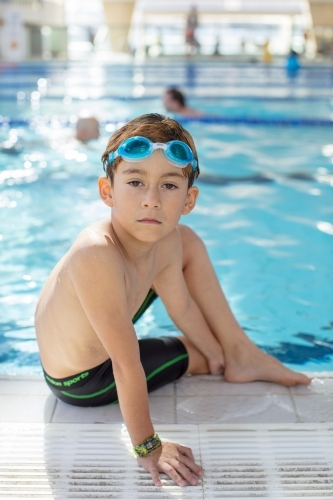 Young boy swimmer sitting at pools edge