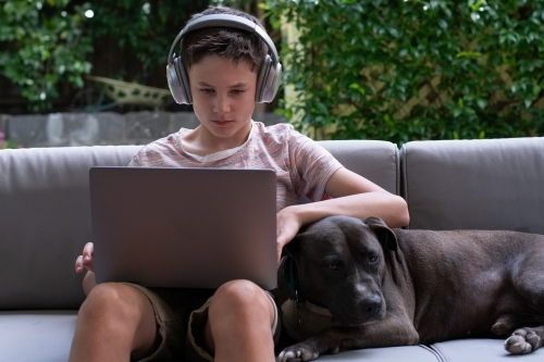 Young boy using laptop outside