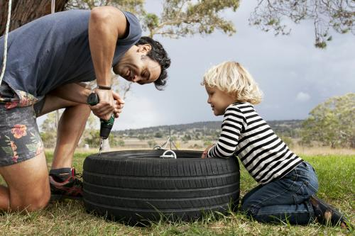 Young boy watching dad using power drill to make tyre swing