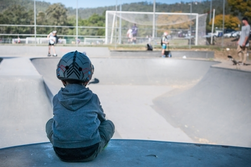 Young boy watching skaters in a skate park
