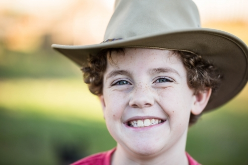 Young boy wearing akubra hat with big smile