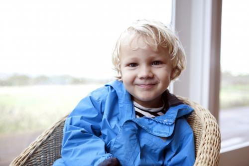 Young boy wearing blue jacket sitting in wicker chair in front of a window