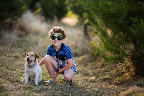Young boy wearing glasses squatting next to dog in pine trees
