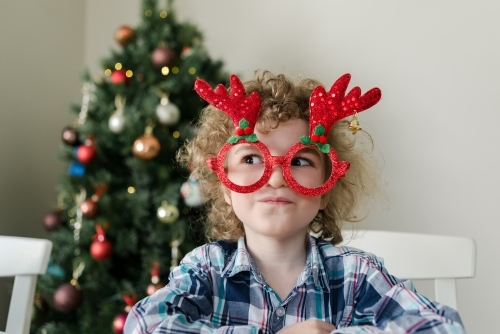 Young boy wearing novelty Christmas glasses, making a funny face