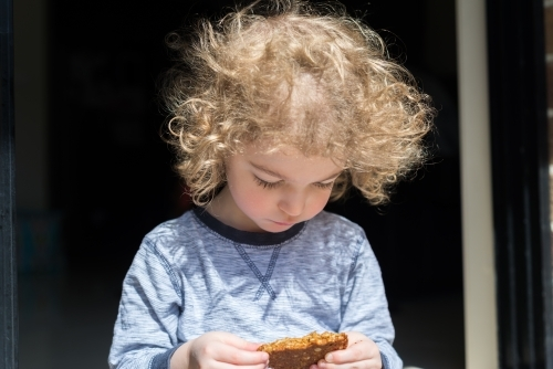 Young boy with a homemade ANZAC biscuit