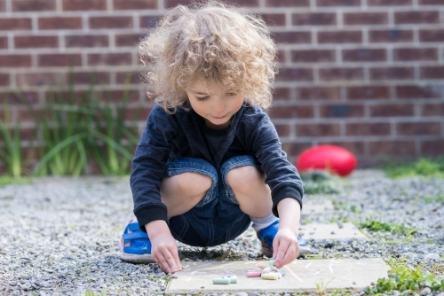 Young boy with AFL football drawing with chalk in the backyard