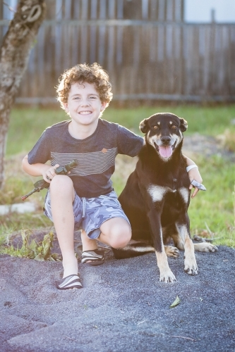 Young boy with arm around black and tan kelpie dog