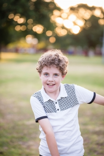 Young boy with curls dancing in park