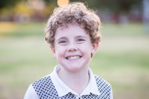 Young boy with curly hair happy smiling